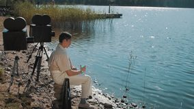 Film producer in hair net eat grapes from speaker on lake shore with two camera. Film producerin hair net and white clothes eat grapes from speaker on lake shore stock video