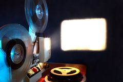 Film Projector. Old 8mm film projector showing the film in dusk onto a wall beside a stack of film reels Royalty Free Stock Images