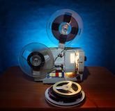 Film Projector. Old 8mm film projector in dusk beside a stack of film reels Royalty Free Stock Photos