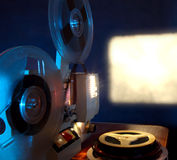 Film Projector. Old 8mm film projector showing the film in dusk onto a wall beside a stack of film reels Stock Images