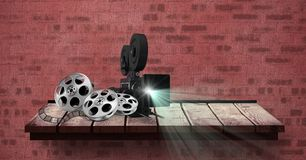 Film projector with reel placed on table against red bricked wall. Digitally generated image of film projector with reel placed on table against red bricked wall Royalty Free Stock Photo
