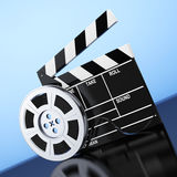 Film Reel with Cinema Tape near Clapboard. 3d Rendering. Film Reel with Cinema Tape near Clapboard on a blue background. 3d Rendering Royalty Free Stock Photos