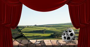 Film reel and curtain with scenic landscape in background Royalty Free Stock Images