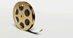 Film reel with a film strip. On the withe background Royalty Free Stock Images