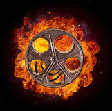 Film reel in fire, isolated on black background. Concept of filmmaking Royalty Free Stock Photos