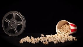 Film reel with popcorn on black. Background stock video