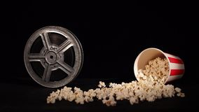Film reel with popcorn on black. Background stock footage