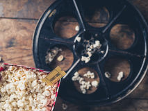 Film reel and popcorn. Cinema concept with vintage film reel, popcorn and a movie ticket Stock Images