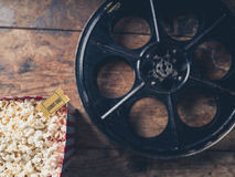 Film reel and popcorn. Cinema concept with vintage film reel, popcorn and a movie ticket Royalty Free Stock Image