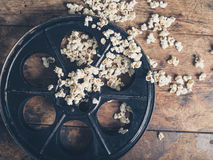 Film reel and popcorn. Cinema concept of vintage film reel with popcorn on wooden surface Stock Images