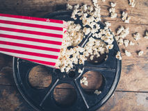 Film reel and popcorn. Cinema concept of vintage film reel with popcorn on wooden surface Stock Photos