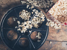 Film reel and popcorn. Cinema concept of vintage film reel with popcorn on wooden surface Royalty Free Stock Photography