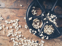 Film reel and popcorn. Cinema concept of vintage film reel with popcorn on wooden surface Stock Image