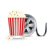 Film reel and popcorn isolated on white. Background Stock Images