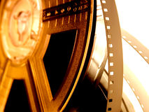 Film reel serie 3. Film reel on golden yellow light. Starting white portion of film strip unwinding stock photo