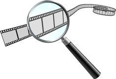 Film Reel under Magnifying Glass Stock Photo