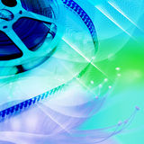 Film Reels. Reel of movie film unwinding, blue filter Royalty Free Stock Images
