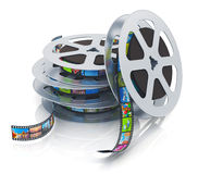 Film reels with filmstrips. Stack of metal film reels with filmstrips with colorful pictures isolated on white background with reflection effect Royalty Free Stock Photos