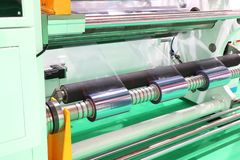Film Roll slitting machine. A shearing operation that cuts a large roll of material into narrower rolls stock images