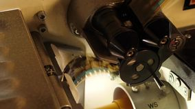 Film runs through a 35mm projector in a movie theater