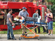 Film shoot location of an accident scene. On location film shooting of an accident scene with a fake injured person on an ambulance stretcher Stock Photos