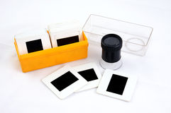 Film slide inspector tool. Photo editing magnifier loupe over stack of old transparency film stock photos