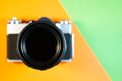 Photo camera on orange and green background stock photography
