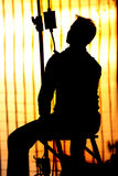 Film Spotboy Silhouette. A film spotboy sit against a bright lighting during a Indian Film shoot Stock Images