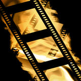 Film strip. Old film strip on a black and gold background Royalty Free Stock Photography