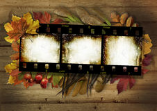 Film strip and autumn border on vintage wooden background Royalty Free Stock Photography