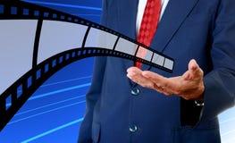 Film strip in businessman hand. Cinema industrial Royalty Free Stock Image