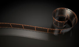 Film Strip Curled. A strip of blank old vintage camera film curled up on an isolaed studio background Royalty Free Stock Photo