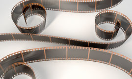 Film Strip Curled. A strip of blank old vintage camera film curled up on an isolaed studio background Royalty Free Stock Images