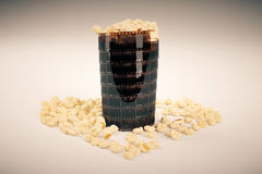 Film strip popcorn cup. Movie lovers concept with film strip popcorn cup on light background. 3D Rendering Royalty Free Stock Photos