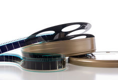 Film Strip, Reel and Can. A container of film strip, film reel and film can on a white background Stock Photos