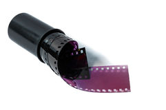 Film strip rolled on canister. Rolled film strip coming out of film canister Stock Photos