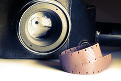 Film strips closeup with vintage movie cinema camera with lens on background Stock Images