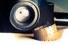 Film strips closeup with vintage movie cinema camera with lens on background Stock Photo