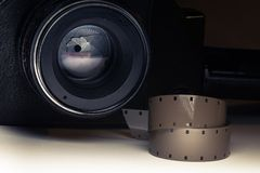Film strips closeup with vintage movie cinema camera in shadow on background Royalty Free Stock Image
