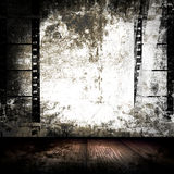 Film Strips Grunge Room. Grunge old, obsolete film strips on old destroyed wall in a room Royalty Free Stock Image