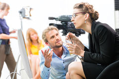 Film team discussing direction for video production. Team or Director discussing during a break the scene direction on set of a commercial video production or Royalty Free Stock Images