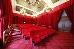 Film theatre with chandeliers and rows of seats. Film theatre with beautiful chandeliers and rows of seats and red curtains Royalty Free Stock Photography