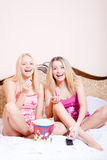Film time: Two girl friends or sisters blond adorable attractive pretty young women sitting in bed with popcorn, watching movie Stock Photo