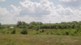 Film van het venster van een bewegende trein De zomer Zonnige dag, bos, machtslijnen stock videobeelden