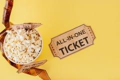 Film?w bilety, film?w paski i popkorn na b??kitnym tle, Odbitkowa przestrze? dla teksta fotografia royalty free