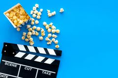 Film watching concept. Clapperboard and popcorn on blue background top view copy space royalty free stock image