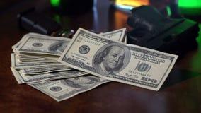 Filma det noir skottet av 100 dollarräkningar som faller i ultrarapid på ett vapen. stock video