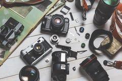 Filma kameror, delar, digitala kameror och linser på trävitt begrepp för bakgrundsteknologiutveckling Arkivbild