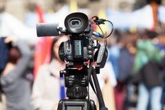 Filmación del reportero de sexo femenino con una cámara de vídeo, muchedumbre borrosa en el fondo Fotos de archivo libres de regalías