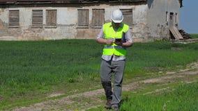 Filmande för byggnadsinspektör på minnestavlaPC nära gammalt övergett skadat hus på gräsfält arkivfilmer